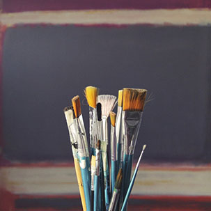 Paintbrushes in front of a canvas